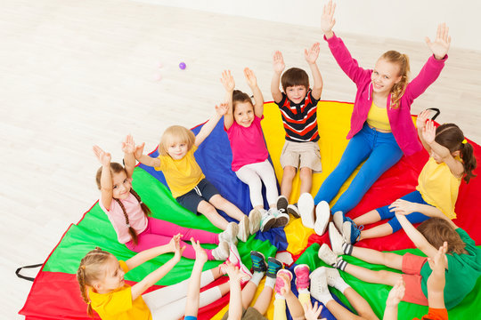 Happy teacher playing circle games with children