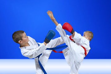 Children athletes are training blows on a light blue background