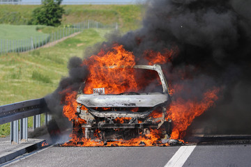 Car burning on a highway with thick black smoke