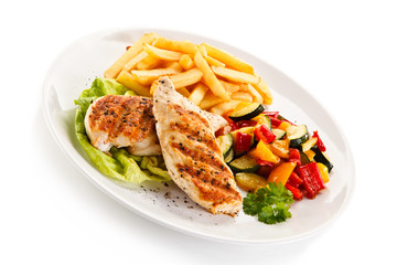Grilled chicken fillet with french fries on white background