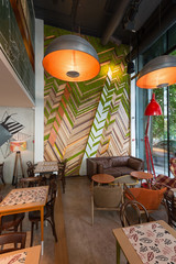 Urban restaurant interior with green plants on the wall