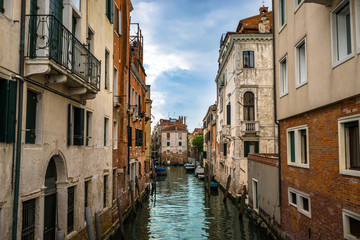 Panoramic view on famous Grand Canal among historic houses in Venice, Italy at cloudy day with dramatic sky, wood bridge and sitting woman on the foreground.