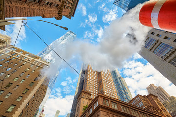 Looking up at Manhattan skyscrapers with steam coming from street pipe, New York City, USA.