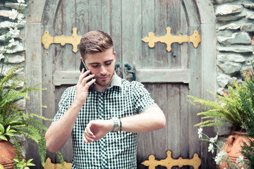 Man standing at garden looking at hand watch and talking phone - Time is money.