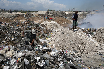 A man searches in a pile of garbage in a dump in Port-au-Prince, Haiti