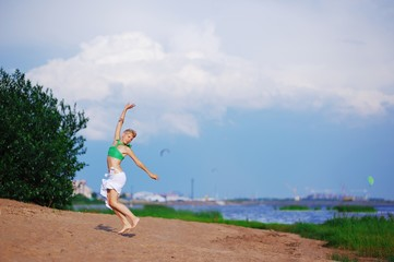 Young slim blonde girl in tank top and skirt dancing on the Bay near the green bushes on blurred background of sky and city.