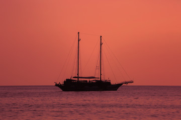 Beautiful red sunset with a sailboat sailing