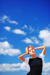 Woman standing outdoors with eyes closed and arms outstretched against the blue sky and beautiful scenic clouds