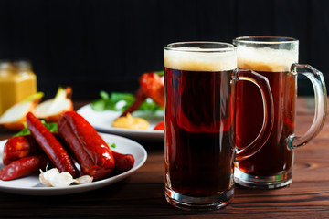 Two mugs of dark beer with crusty grilled chicken wings and various sausages.