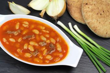 Traditional Turkish cuisine. Kuru Fasulye . Haricot Bean with onion, scallion and rustic bread on black stone background.