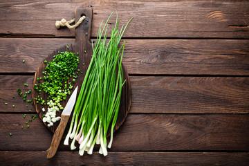 Fototapeta Green onion or scallion on wooden board, fresh spring chives obraz