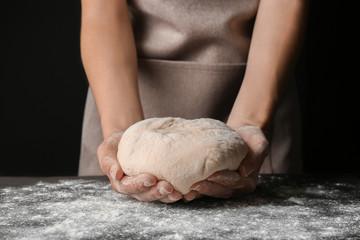 Female hands holding dough