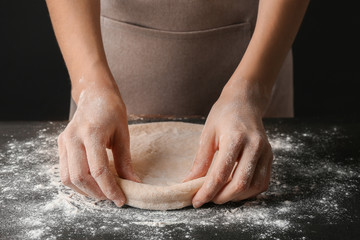 Female hands making dough for pizza on black table