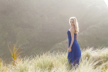 outdoor portrait of young beautiful woman in blue gown posing on natural background