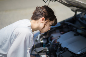 young woman checking under the hood.