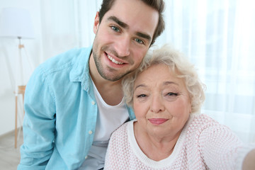 Young man taking selfie with grandmother at home