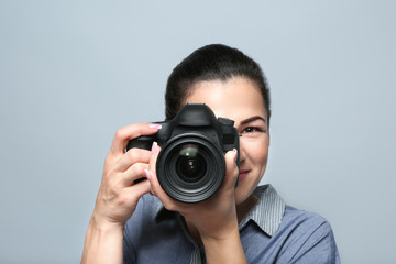 Portrait of beautiful young photographer on grey background