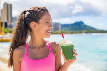 Sport fitness woman drinking healthy green detox juice, vegetable smoothie at running workout on beach summer outdoors. Fitness healthy lifestyle. Waikiki, Honolulu, Hawaii.