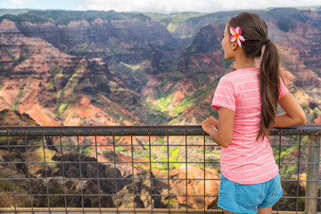 Wall Mural - Hawaii nature travel girl looking at Kauai mountains canyon. Hiker woman tourist enjoying lookout at Waimea Canyon, popular tourist destination.
