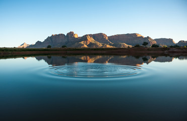 Calm ripples reflecting the red cliffs Wall mural