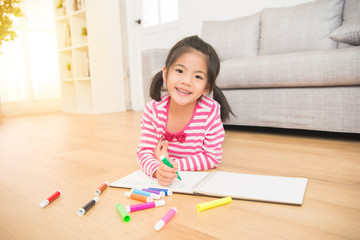 Little child girl draws with colored pencils
