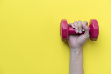 woman hand holding red dumbbell on yellow background