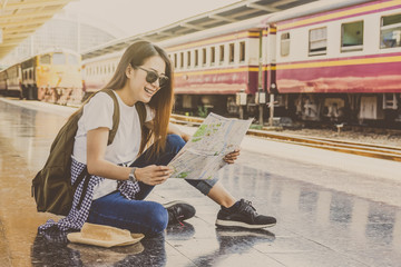 Asian woman Traveler are looking at the map and smiling with happiness action at the train station, Travel and transportation concept