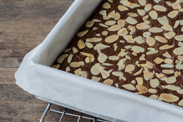 Homemade dark chocolate brownies topping almond slices in square tray cover baking sheet on cooling rack put on wood table for coffee break or tea time.Brownies is one type of popular chocolate cake.