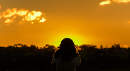 One female with long hair is sitting alone looking into the sun in silhouette