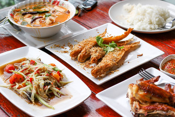 Thai food, papaya spicy salad with grilled chicken and fried fish