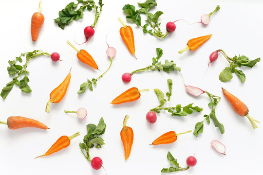 Vegetables isolated on white background. Food pattern of vegetables: carrots, radishes, green tops. Top view.