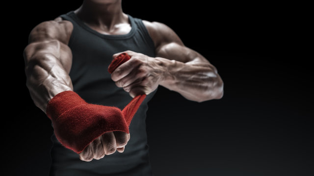 Close-up photo of strong man wrap hands on black background with copy space for text