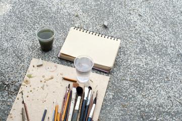 Pencils and brushes of the artist lie on asphalt