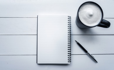 Top view desk office with notepaper,pen,coffee in white background.