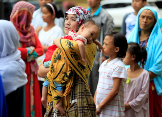 Evacuees participate in a flag raising to mark Independence Day in Marawi City