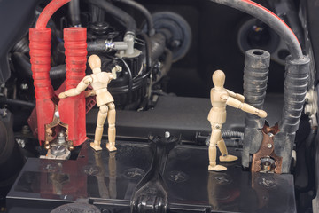 Wood Mannequin are Repairing Car Battery Work concept.
