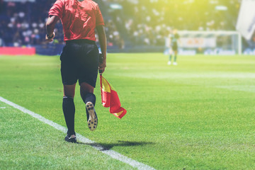 Lineman assistant referee with flag running at beside of a soccer field.