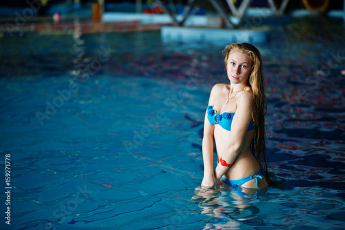 d42d81f65a7b6 Portrait of an attractive young girl standing and posing in the pool  wearing blue bikini in the water park.