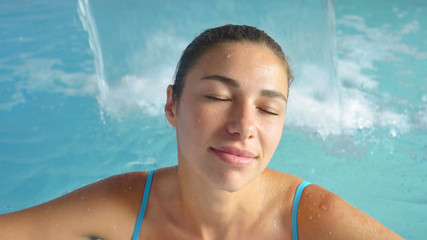 Beautiful young girl (woman) relaxed in a hydromassage bath, in a blue bathing suit, on a blue background. Concept: spa procedures, body massages, spa cream, relax, spa water treatments, swimming pool