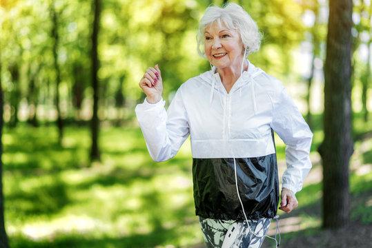 Jolly senior woman enjoying running in forest