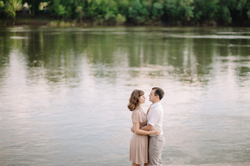 love story, beautiful couple a man and a woman in bright clothes, happy family, walking along the river Bank,standing holding hands, looking at each other, hugging, summer, nature