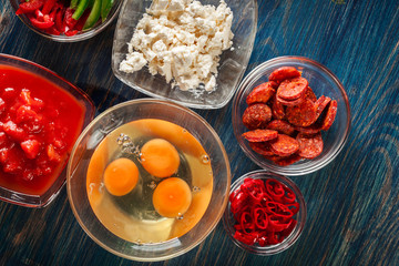 Ingredients for preparing frittata - eggs, sausage chorizo, red