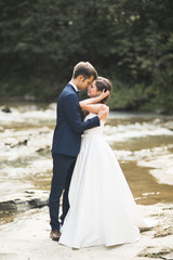 Elegant gentle stylish groom and bride near river with stones. Wedding couple in love