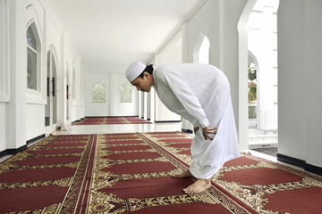 Young asian muslim man is praying to god