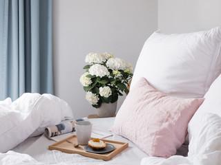 frühstück im Bett mit Holztablett, Zeitung und Blumen