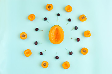 Colorful summer fruits pattern with melon slices, apricots and cherries isolated on azure aquamarine background