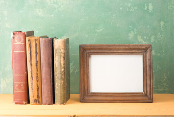 A shelf with books and  empty picture frame