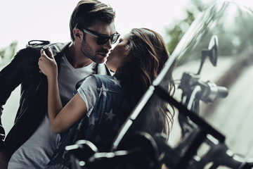 Beautiful stylish young couple hugging and kissing on motorcycle outdoors
