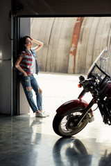 Stylish young woman in denim vest standing in garage and looking at motorbike