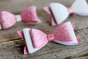 Nice hair bows accessories made of light pink and white felt with sequins. Hair bows for girls on an old wooden table. Closeup